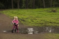 A young girl learning to cycle royalty free stock photos