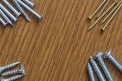 Gwoździe i śruby na drewnianym tle z kopii przestrzenią Zdjęcie Stock