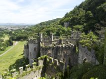 Gwrych castle in Wales UK surrounded by trees and foliage on hill side - Full ruins overlooking the town of Aberegele with mountai Stock Images