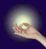 Gyan Mudra and the Flower of Life Symbol. Female hand making Gyan Mudra hand position with the Flow of Life symbol in the background and a pale lemon glow Stock Photo