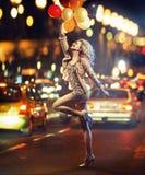 Gyckel-älska flickan som rymmer en grupp av ballonger Arkivbild