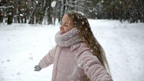 Gyckel i vinterskogen - flicka som rotera under fallande rimfrost arkivfilmer