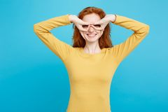 Gyckel och folkbegrepp - Headshotstående av den lyckliga ljust rödbrun röda hårflickan med fräknar som ler och gör fingerexponeri Arkivfoton