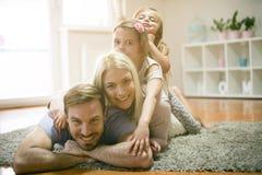 Gyckel på golv Familj som ser kameran arkivfoton