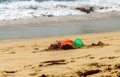 Gyckel på stranden med hinkar arkivfoton