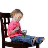 gyckel som har hon själv den sittande litet barn för målning Arkivbilder