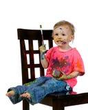 gyckel som har hon själv den sittande litet barn för målning Arkivfoton