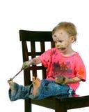 gyckel som har hon själv den sittande litet barn för målning Royaltyfri Fotografi