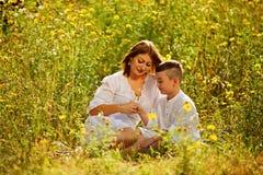 gyckel som har modersonen Son som ger blommor till hans moder henne skjutit utomhus- för ö för fall dimmigt Royaltyfri Bild