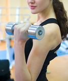 In The Gym. A young attractive girl swings his hands through the Dumbbell in the gym Stock Images