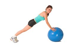Gym. Woman in gym wear bending down on blue ball Stock Photography