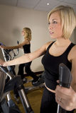 At The Gym. Two beautiful young women working out on cross training machines at the gym Stock Photo