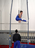 At the gym. Young gymnast practicing on rings Stock Image