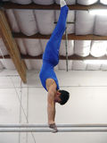 At the gym. Young gymnast competing on parallel bars Royalty Free Stock Photo