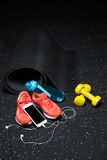 Gym accessories for sport training. Dumb-bells, bottle, and sport shoes with a  phone on a floor background. Copy space. A close-up of black streching mat, blue Stock Images