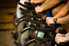 In the gym - Active Lifestyle 2. Active Lifestyle - Men & women pedalling on stationery bikes - Shallow DOF Focus on the hand with the watch royalty free stock image