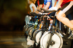 In the gym - Active Lifestyle 3. Active Lifestyle - Men & women pedalling on stationery bikes - Shallow DOF Focus on the second bike royalty free stock photography