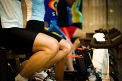 In the gym - Active Lifestyle 4. Active Lifestyle - Men & women pedalling on stationery bikes - Shallow DOF Focus on the 1st person/bike royalty free stock photos