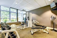Gym in apartment building with brown wall and TV. Royalty Free Stock Photo
