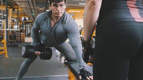 In the gym - athlete man lifting dumbbells. In the gym - muscular athlete men lifting dumbbells Stock Images