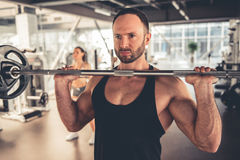 At the gym. Attractive sports people are working out with barbell in gym Royalty Free Stock Photo