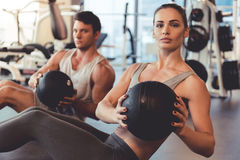 At the gym. Attractive young muscular men and women are working out with balls in gym royalty free stock image