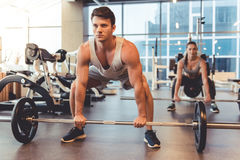 At the gym. Attractive young people are working out with barbell in gym stock photography