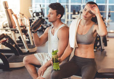 At the gym. Attractive young sports people are drinking water while resting in gym stock photos