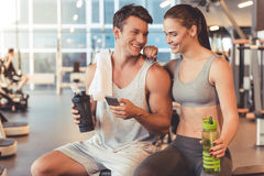 At the gym. Attractive young sports people are holding bottle of water, talking and smiling while resting in gym stock photos
