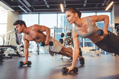 At the gym. Attractive young sports people are working out with dumbbells in gym stock photo