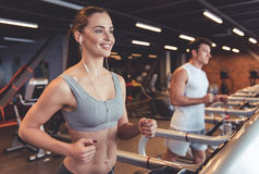 At the gym. Attractive young women in earphones is smiling while running on a treadmill in gym royalty free stock image