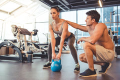 At the gym. Attractive young women is working out with kettlebell in gym, handsome muscular trainer is helping her Stock Image