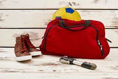Gym bag with soccer ball. Sneakers and pump on wooden table. Sportswear and equipment for physical activity stock images