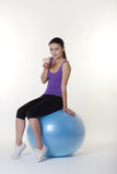 The gym ball. Beautiful Young Woman choosing if she should work out on her gym ball or eat a nice unhealthy cake Stock Photo