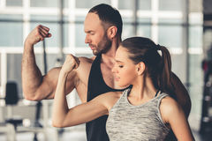 At the gym. Beautiful sports couple is showing their muscles while standing in gym royalty free stock image