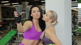 In gym beautiful women take a photo of themselves on the phone. Two female girlfriends with sports body shapes make a shutter on smartphone and watch result on stock video
