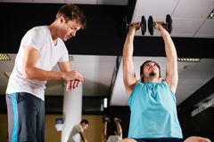 Gym buddies working out in gym timing exercise Royalty Free Stock Photography