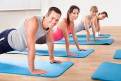 Gym class doing press ups. Group of diverse healthy people in a gym class doing press ups while exercising on two rows of blue mats on a wooden floor Stock Photo