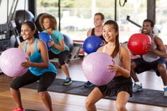 Gym class doing squats. Multi-ethnic gym class doing squats with medicine balls Stock Photo