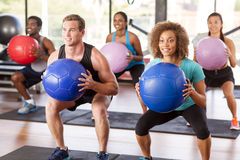Gym class doing squats. Multi-ethnic gym class doing squats with medicine balls Royalty Free Stock Photography