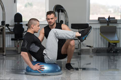 Gym Coach Helping Man On Bosu Abs Exercise. Personal Trainer Showing Young Man How To Train On Bosu Abs Exercise In A Health And Fitness Concept Royalty Free Stock Photos