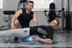 Gym Coach Helping Man On Bosu Abs Exercise. Personal Trainer Showing Young Man How To Train On Bosu Abs Exercise In A Health And Fitness Concept Royalty Free Stock Image