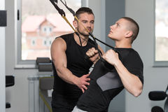 Gym Coach Helping Man On Trx Fitness Straps Stock Images