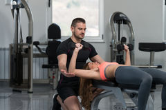 Gym Coach Helping Woman On Chest Exercise Stock Images