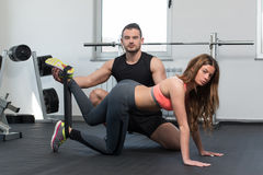 Gym Coach Helping Woman With Resistance Bands Stock Photo