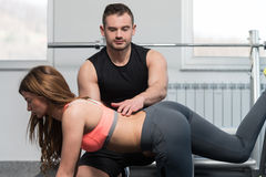 Gym Coach Helping Woman With Resistance Bands Royalty Free Stock Photography