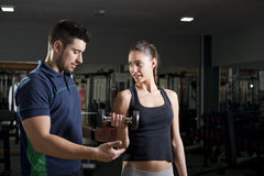 Gym coach training woman exercises at gym Royalty Free Stock Image