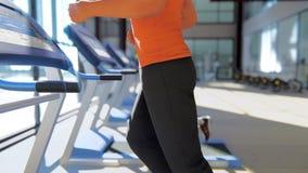 Gym com as máquinas diferentes do exercício nele e um desportista que corre na escada rolante ilustração stock