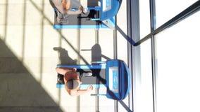 Gym com as várias máquinas do exercício nele e os povos que andam na escada rolante no dia ensolarado ilustração royalty free
