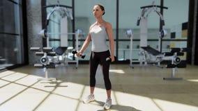 Gym com uma variedade de equipamento do exercício e um desportista que faz esportes ilustração stock